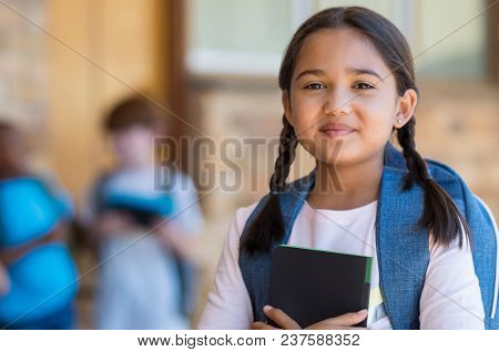 Smiling student girl wearing school backpack and holding exercise book. Portrait of happy asian young girl outside the primary school. Closeup face of smiling hispanic schoolgirl looking at camera.
