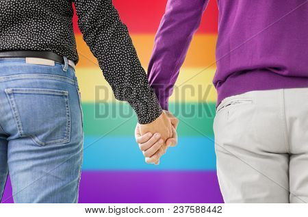 same-sex relationships, lgbt and homosexual concept - close up of male gay couple holding hands over rainbow background