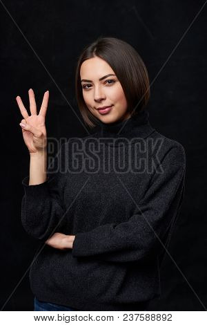 Hand Counting - Three Fingers.smiling Woman In Grey Turtleneck Sweater Over Dark Background Showing