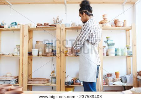 Young African American male potter in apron putting workshop in order while standing by shelf with handicrafts and equipment