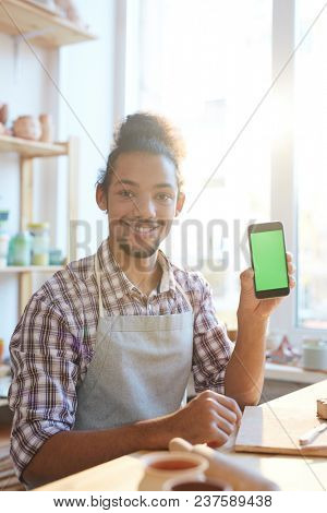 Portrait of young mixed race craftsman in apron sitting at table in workshop, holding smartphone and smiling at camera