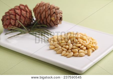 Pine nuts and pine cones on a white cutting board