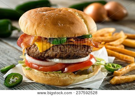A Delicious Burger With Bacon, Cheddar, Jalapeno Pepper, Tomato, Onion, Pickle And Lettuce With Fren
