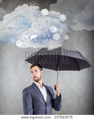 Businessman Holding Cloud With Different Digital Icons. Technology Concept.