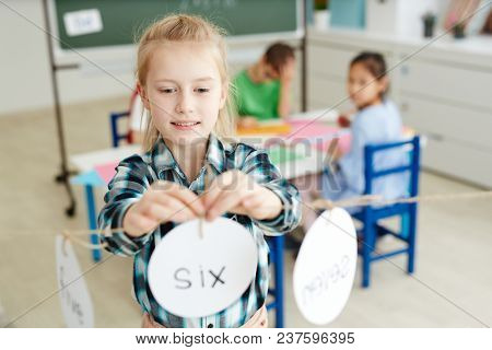 Cute blond primary schoolgirl playing math game while having indoor activities with classmates after lessons