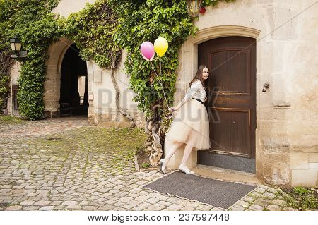 Young Woman With A Colorful Balloons Opens Door.