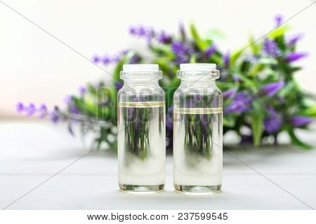 Two Glass Bottles With Oil In It And Lavender Flower On The Background On A White Wooden Table