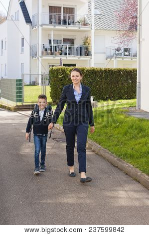 Happy Mother And Son Going To School. Looking At Camera.