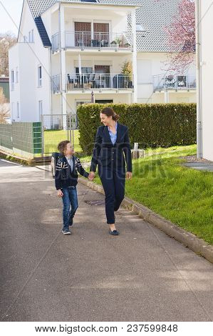 Happy Mother And Son Going To School. Look At Each Other