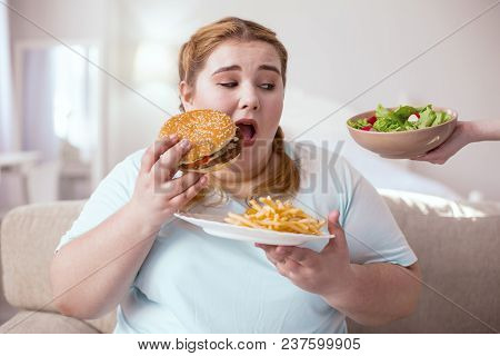 Junk Food. Fat Young Woman Eating Unhealthy Food While Thinking About Nice Green Salad
