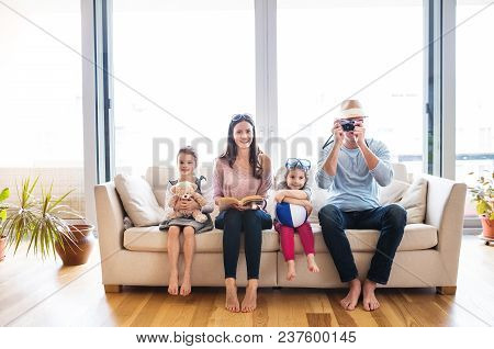Portrait Of A Young Happy Family With Two Children Getting Ready For Holiday At Home.