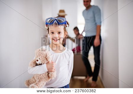 Young Family With Two Children Going On A Holiday, Walking Through The Corridor.