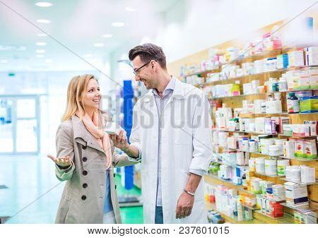 Handsome Male Friendly Pharmacist Serving A Female Customer.
