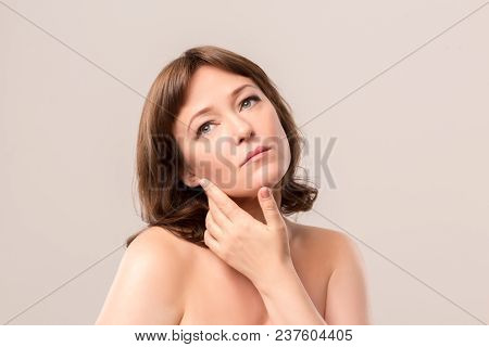 Nice Woman With Thoughtful Face Touching Her Cheeck. Isolated On White Background. Mid Age Woman Ove