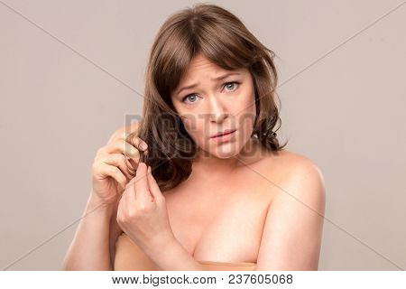 Nice Lady With Upset Face Expression Showing Her Damaged Hair. Standing On White Background. Mid Age