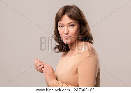 Mid Age Woman Over 35 Years Old Beauty Concept. Luxury Woman In Beige Blouse Standing Half Turn And