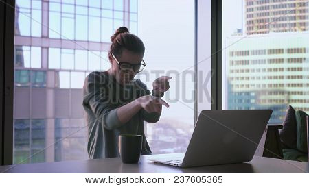 Business Woman With Arms Raised Is Celebrating Success. Attractive Female Freelancer In Glasses Is S