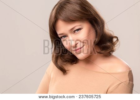 Beautiul Brunette With Natural Makeup Standing In White Studio. Having Deep Look. Mid Age Woman Over
