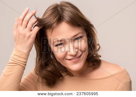 Smiling Brunette In Beige Blouse Touching Her Fringe. Beauty Concept. Mid Age Woman Over 35 Years Ol