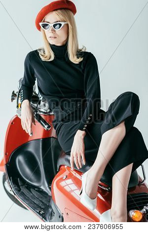 Attractive Young Woman In Black Clothes Posing By Vintage Scooter Isolated On Grey