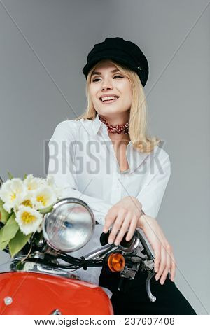 Attractive Young Woman  In White Shirt Posing On Red Scooter With Tulips Isolated On Grey
