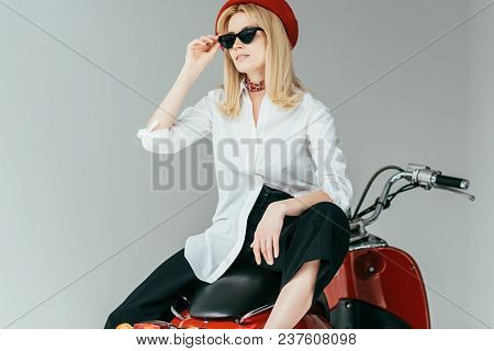 Attractive Young Woman Sitting On Retro Scooter Isolated On Grey