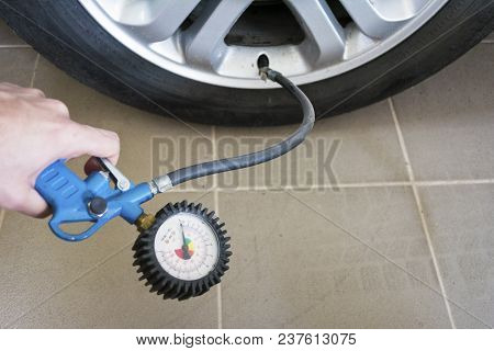 Close Up Mechanic Inflating Tire And Checking Air Pressure With Gauge Pressure.