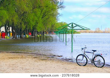 Lonely Bicycle Standing On Beach During Flooding On City Beach. Empty Beach Awnings Flooded With Wat