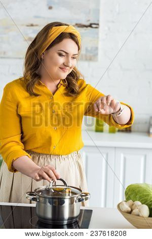 Attractive Woman Checking Time On Wristwatch Near Pan On Electric Stove In Kitchen