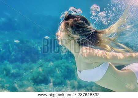 Girl And Small Fish Swimming Underwater Portrait. Sea Summer Blue Water Background With Bubbles. Sof