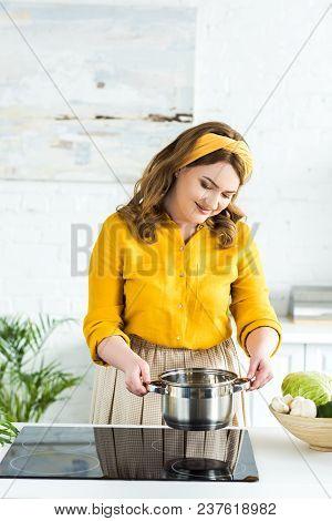 Beautiful Woman Putting Pan On Electric Stove In Kitchen