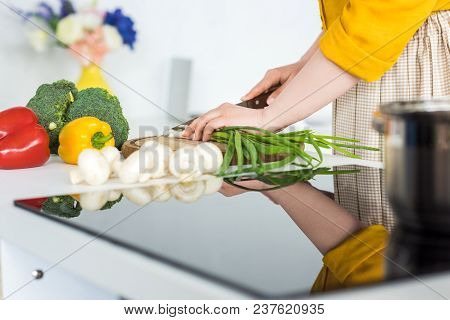 Cropped Image Of Woman Cutting Green Onion In Kitchen