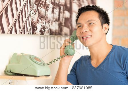 The Man Pick Up Talking On A Green Wired Phone.