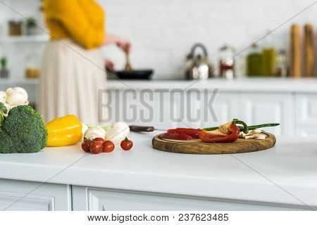 Cropped Image Of Woman Cooking At Kitchen With Vegetables On Foreground