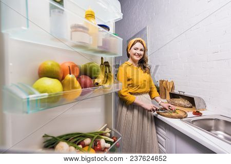 Beautiful Woman Cutting Vegetables And Looking At Camera At Kitchen