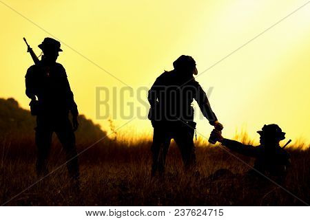 Silhouette Of Military Soldier Holding Weapons Overhead After Get Victory Of War At Sunset. Giving A