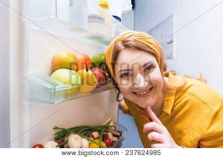 Smiling Beautiful Woman Looking At Camera Near Open Fridge At Kitchen