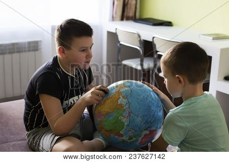 Boys With Globe Think Where To Go On Vacation