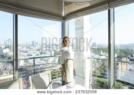 Woman Standing At Restaurant Near Window With Buildings In Background. Concept Of Catering Establish