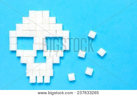 Refined Sugar On Blue Background.sugar Cubes In Form Of Skull.concept Of Healthy Eating, Addiction T