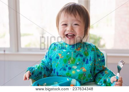Happy Toddler Boy Eating Dinner In His Highchair