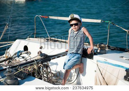 Cute Little Boy Wearing Captain Hat Aboard Luxury Yacht In Summer