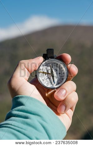 Close-up A Man's Hand Holds A Pocket Compass Against The Backdrop Of Mountains And Woods. The Concep