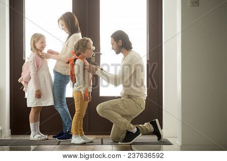 Caring Parents Helping Happy Kids Put Backpack On Preparing Go To School Standing At House Hall Toge