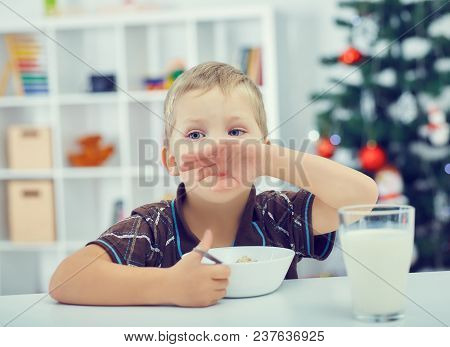 Little Boy Eating Breakfast On The Eve Of The New Year. Christmas Tree In The Background.