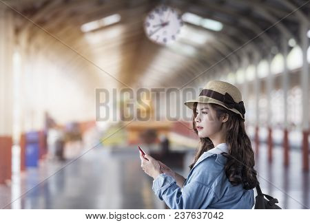 Beautiful Woman With Backpack Standing And Using Smartphone At Railway Station