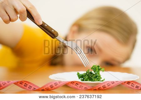 Sad Young Blonde Woman Dealing With Anorexia Nervosa Or Builimia Having Small Green Vegetable On Pla
