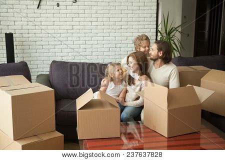 Happy Parents With Kids Embracing On Sofa In Living Room With Many Boxes, Smiling Family Hugging Chi
