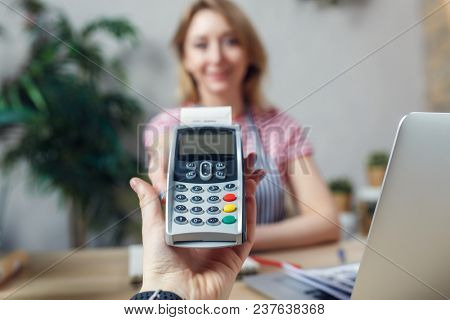 Picture of florist with calculator at table with laptop