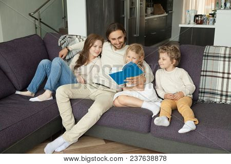 Happy Young Family With Children Reading Book Together Sitting On Sofa At Home, Smiling Parents Rela